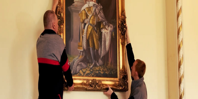 two removalists removing antique painting from the wall