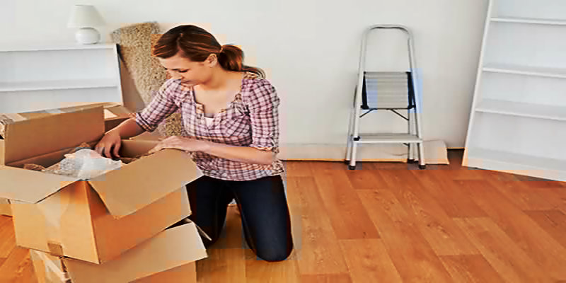 young woman packing her belongings in cardboard boxes