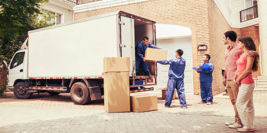 three men load packed boxes inside a moving truck while a young couple is watching them