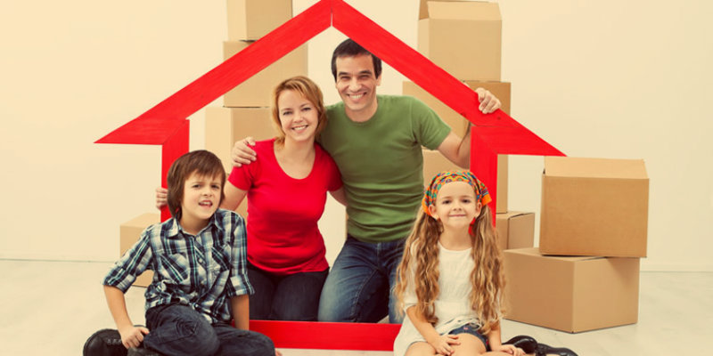 happy family of four preparing for a move with cardboard boxes all over
