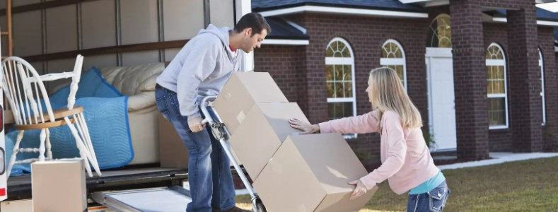 a couple is loading a moving truck