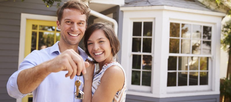 a couple is holding keys of their new house