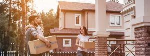 young couple with cardboard boxes relocating into their new house