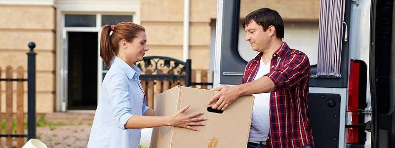 young couple loading a moving van with their household items